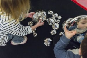 Picture of children seeing their reflection looking into mirrored pebbles