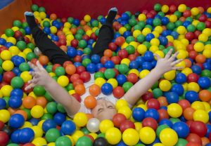 Child lying in ball pit with multicoloured balls