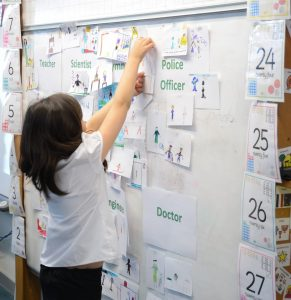 Primary child putting work on a board