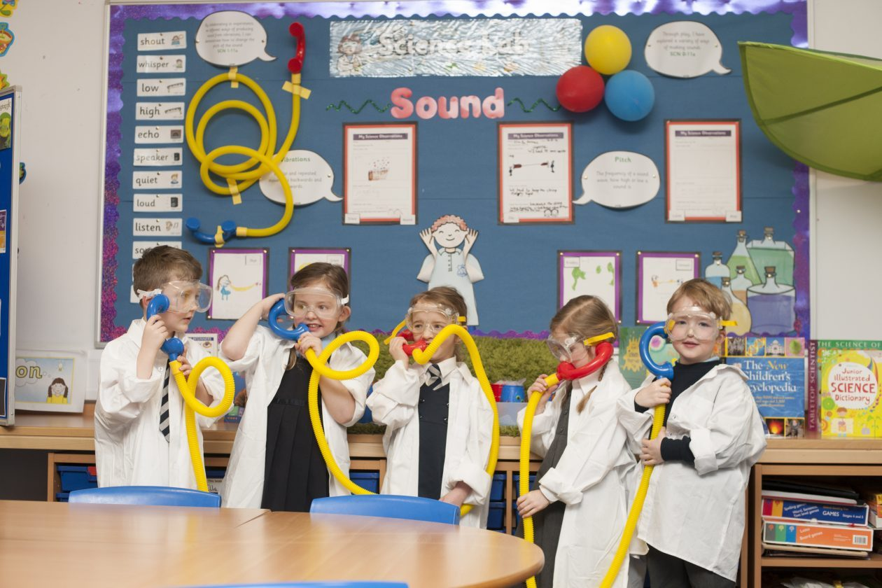 young learners using plastic tubes for pretend telephones