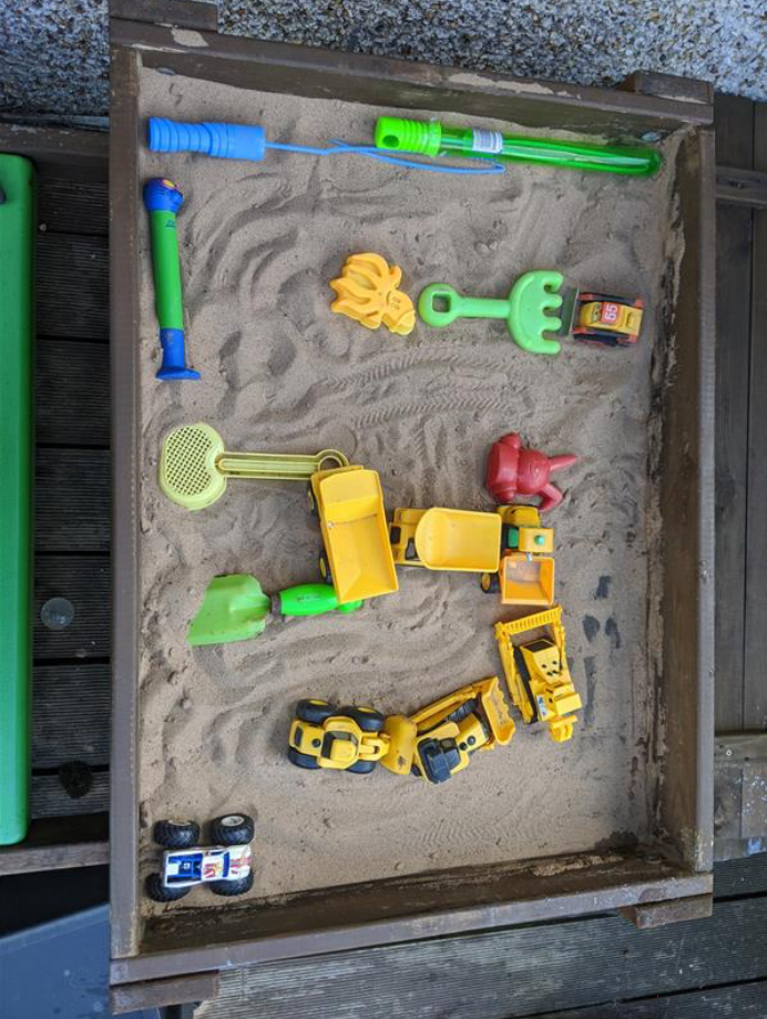 maze in sand pit created with assorted plastic toys