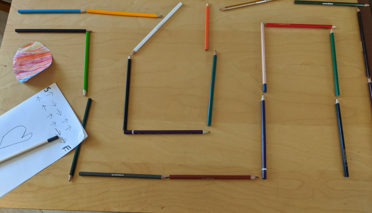 using pencils laid out on table to create a maze