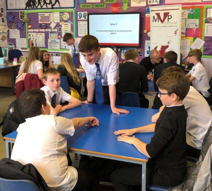 Older learner talking to 4 younger pupils
