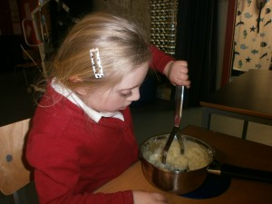 Aria helping to mash potatoes for our Burns Supper.